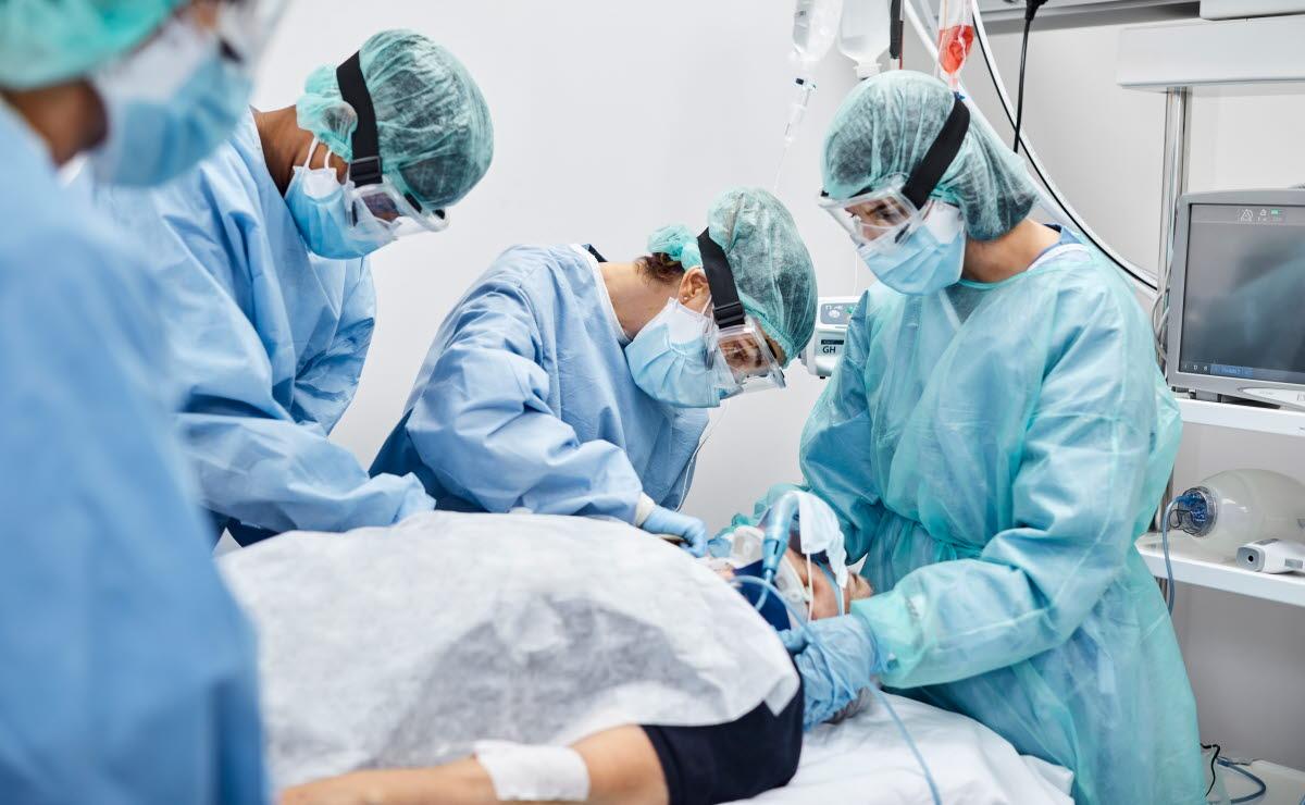 Helsepersonell tar seg av en covid-19-pasient ikledd smittervernutstyr